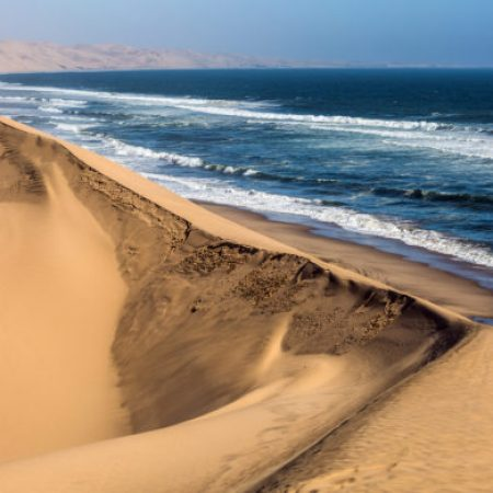 Atlantic coast of Walvis Bay, Namibia, south of Africa. Ocean surf with foamy waves. Jeep - safari through the huge sand dunes. The concept of extreme and exotic tourism