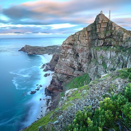 Cape Point South Africa as time stands still - slight movement in the water and clouds as the sun rises in the back. There's a lighthouse on top of the cliff which serves to warn passing ships that there's land.